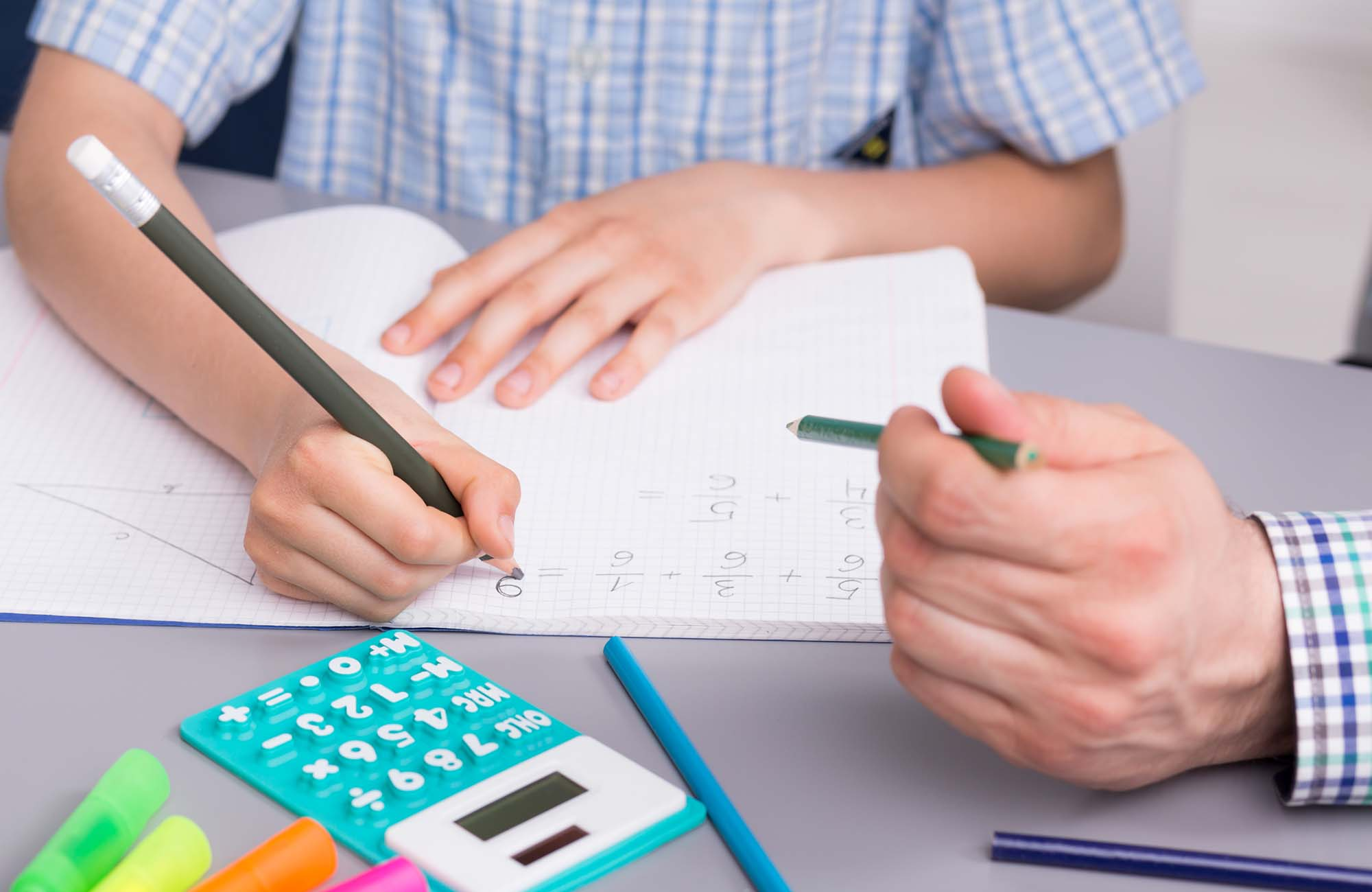 Close up of a small boy studying math with a private teacher, doing notes in his notebook